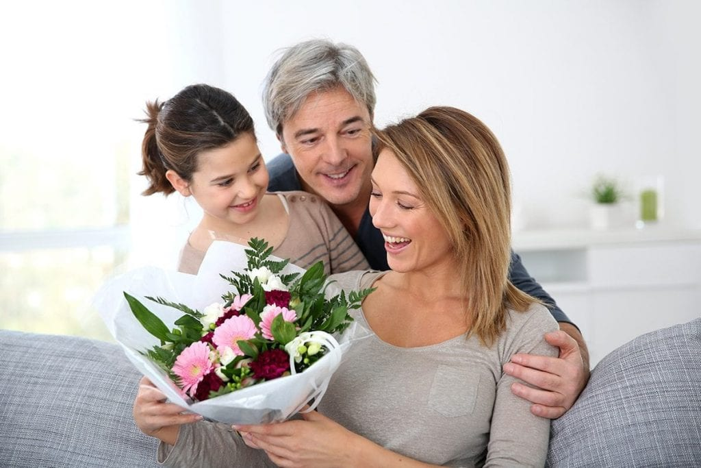 husband and daughter presenting flowers to the wife, mother