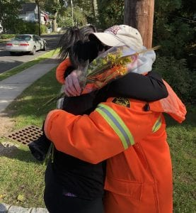 A crossing guard in Chatham, New Jersey, gets a hug and flowers from Sunnywoods Florist.