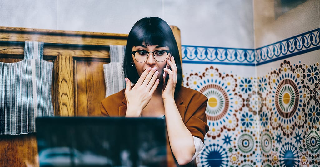 Shocked hipster girl feeling excited of receiving news about upcoming discount during cellphone call with customer service