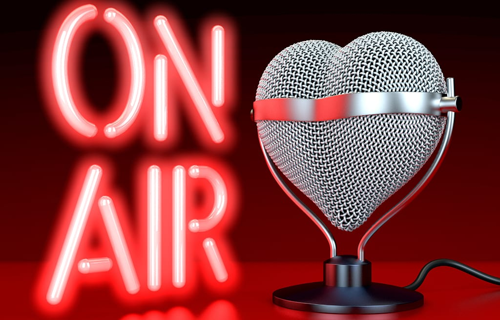 Heart shaped microphones on reflecting, red surface in front of, lateral to neon sign